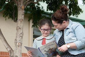 student reading book with teacher