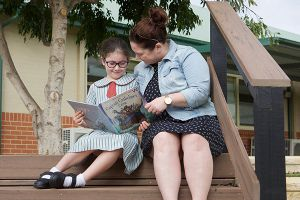 teacher and student sitting on steps reading a book